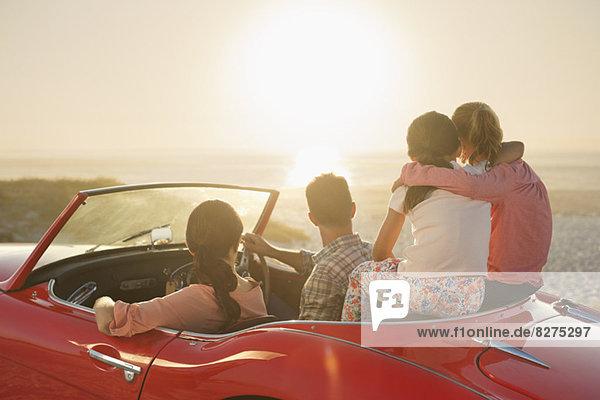 Familie beobachtet Sonnenuntergang über dem Meer vom Cabrio am Strand aus