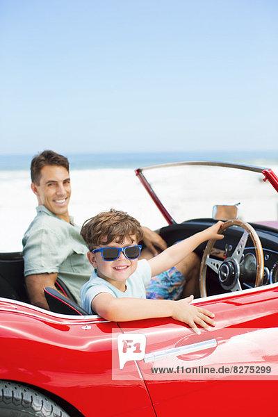 Junge sitzt am Steuer eines Cabrios mit Vater am Strand