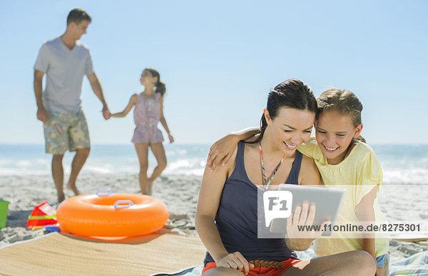 Mutter und Tochter mit digitalem Tablett am Strand