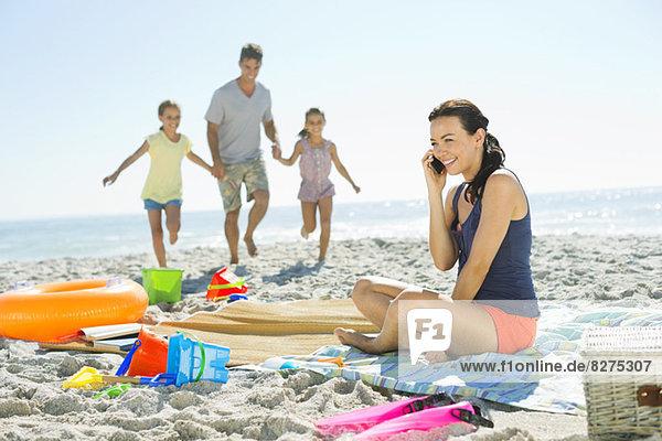 Frau beim Telefonieren am Strand