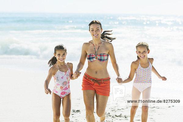 Mutter und Töchter beim Händchenhalten und Laufen am Strand