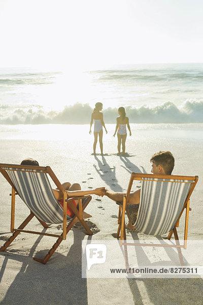 Eltern beobachten Töchter am Strand bei Sonnenuntergang
