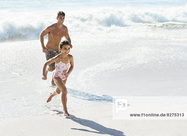 Vater und Tochter beim Surfen am Strand