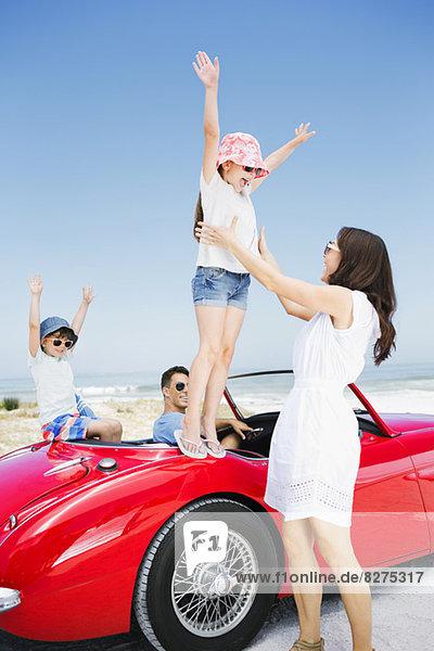 Mädchen  das vom Cabriolet am Strand in die Arme springt.