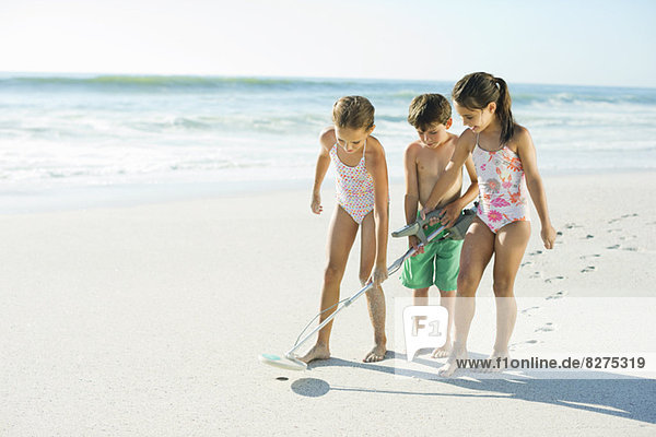 Kinder mit Metalldetektor am Strand