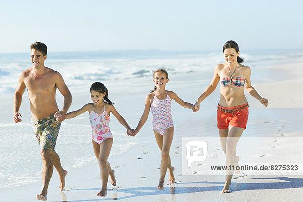 Familie beim Händchenhalten und Laufen am Strand