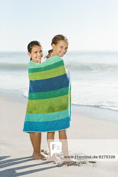 Mädchen in Handtuch gewickelt am Strand