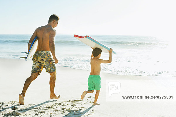 Vater und Sohn mit Surfbrett und Bodyboard am Strand
