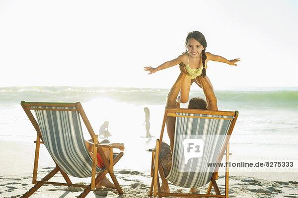 Vater hebt Tochter am Strand auf