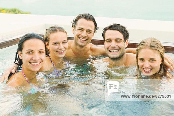 Freunde lächeln zusammen im Whirlpool