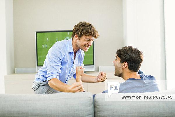 Männer jubeln und schauen Fußballspiel