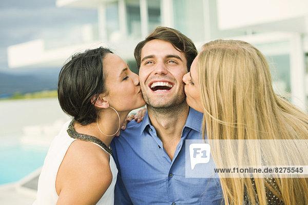 Frauen  die die Wange eines Mannes im Freien küssen.