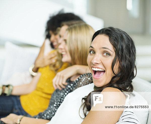 Begeisterte Frau auf dem Sofa mit Freunden