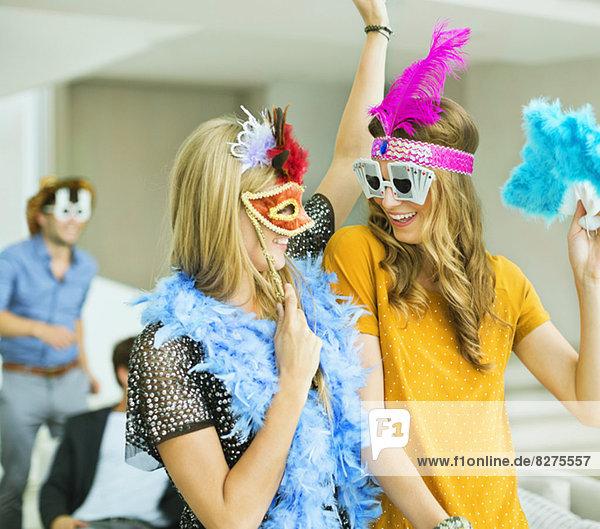 Frauen mit dekorativen Brillen und Kopfbedeckungen auf der Party