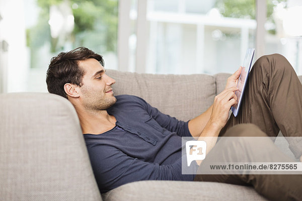 Man using digital tablet on sofa