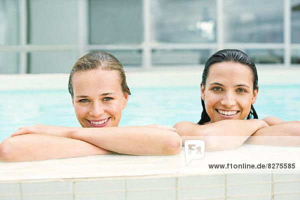 Porträt von lächelnden Frauen am Rande des Swimmingpools