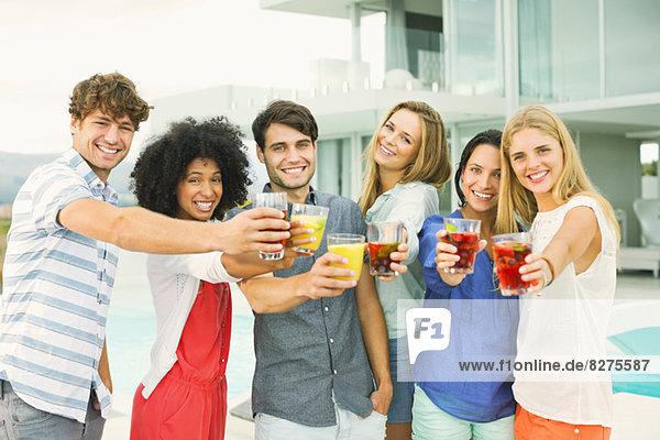 Freunde toasten Cocktails auf der Terrasse