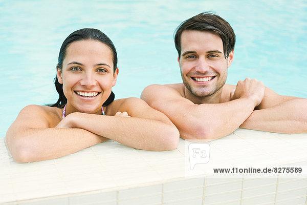 Porträt eines lächelnden Paares  das sich am Rand des Swimmingpools lehnt.