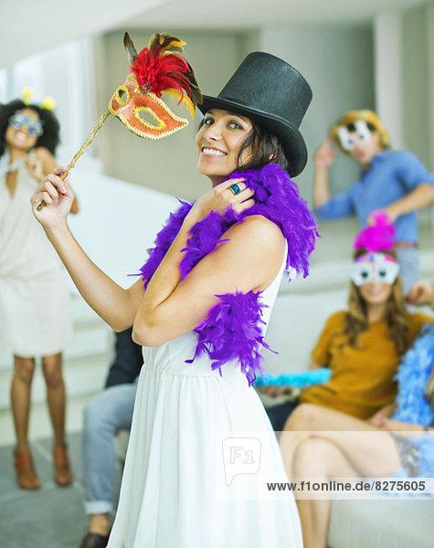 Frau mit dekorativem Hut und Maske auf der Party