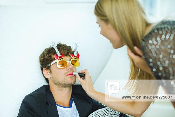 Frau beim Auftragen von Lippenstift auf den schlafenden Mann auf der Party
