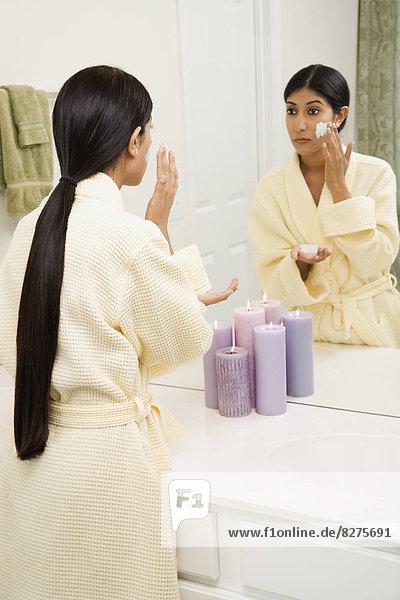 junge Frau junge Frauen eincremen verteilen sehen Gesichtsausdruck Gesichtsausdrücke Ausdruck Ausdrücke Mimik schrubben auftragen Spiegel