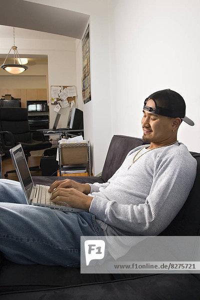 sitzend Mann Notebook Couch junger Erwachsener junge Erwachsene Mütze rückwärts jung tippen Kleidung Erwachsener
