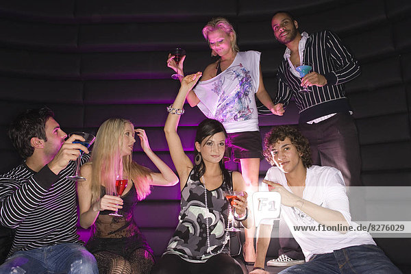 Young couple dancing in a nightclub with their friends having drinks