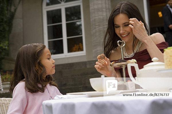 Mutter und Tochter am Gartentisch