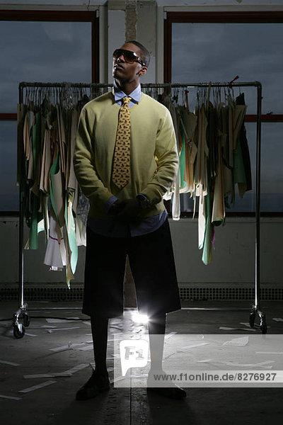 Junger Mann Stand vor einem Kleidung-rack