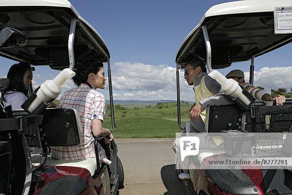 Ansicht der Paare sprechen von ihren Golf-Carts.