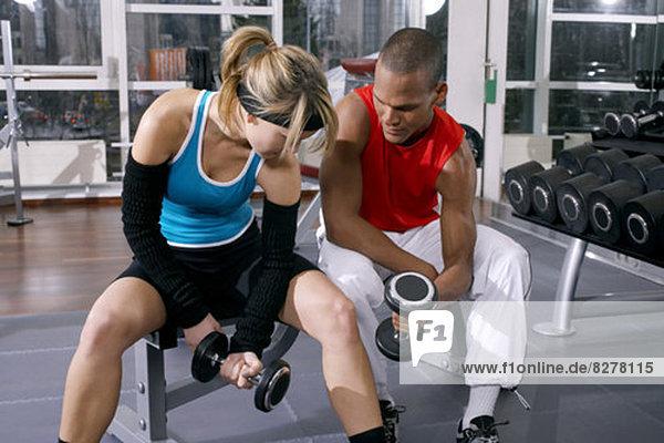 Frau und Mann trainieren mit Hanteln