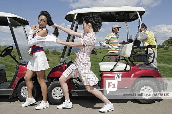 Ansicht von vier Personen  zwei Mädchen kämpfen