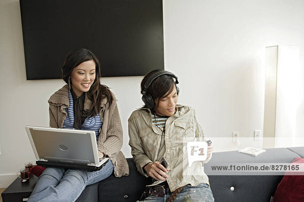 Weiblich working auf Laptop mann Musik zu hören