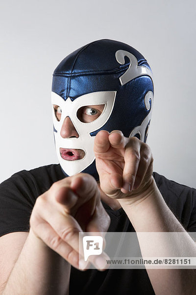 A man wearing a Lucha Libre wrestling mask and gesturing bizarrely with his hands