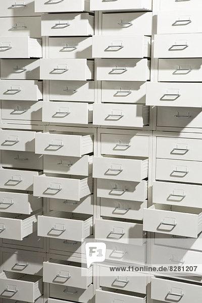 Ein weißer Schrank mit unterschiedlich stark geöffneten Schubladen