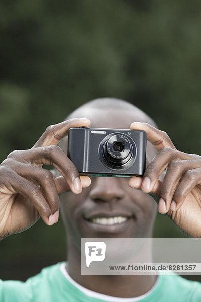 Mann fotografiert mit Digitalkamera