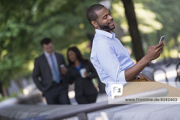 Sommer in der Stadt. Ein junger Mann in grauem Anzug und blauer Krawatte geht mit einer Frau im Anzug spazieren. Ein Mann auf einer Bank sitzend.