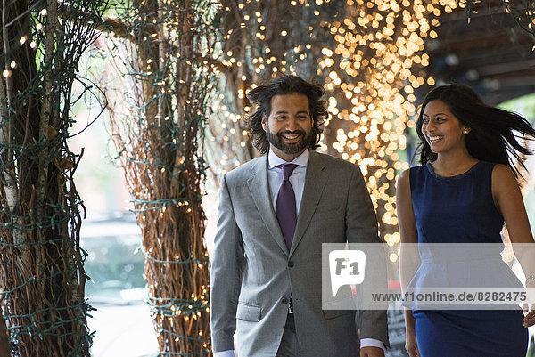 Geschäftsleute. Zwei Menschen  ein Mann und eine Frau  die Hände halten und unter einer Pergola hindurchgehen  beleuchtet mit Feenlicht.
