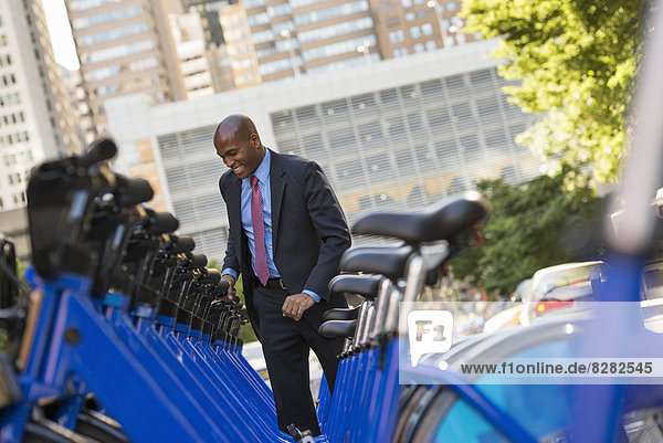 Business People. A Man In A Business Suit Beside A Rack Of Rental Bicycles.