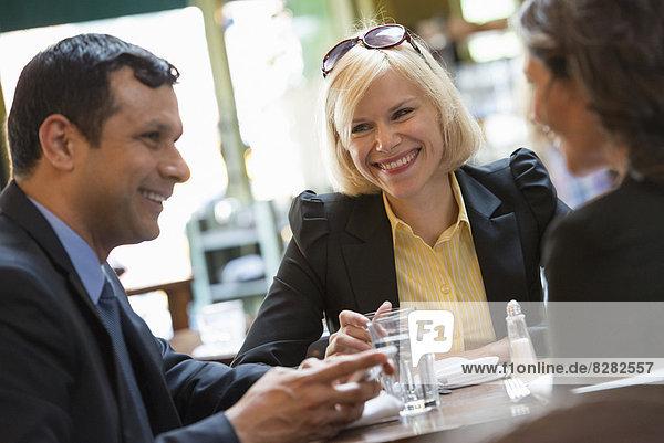 Geschäftsleute. Drei Personen  ein Mann und zwei Frauen sitzen an einem Tisch.