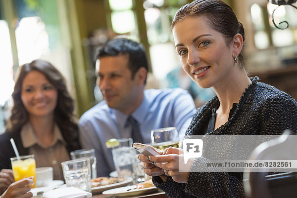 Business People. Three People Around A Cafe Table  One Woman Turning Around  Holding A Wine Glass.