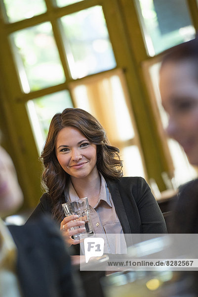Business People. Three People Around A Cafe Table. A Woman Looking Up And Smiling Holding A Glass.