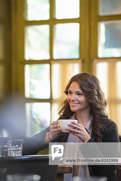 Business People. A Woman In A Grey Jacket Holding A Coffee Cup  Seated At A Table.