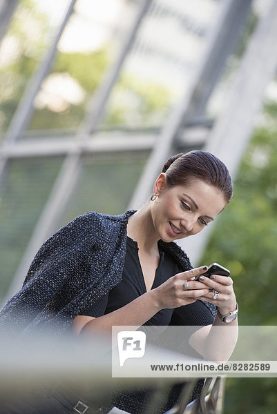 Business People. A Woman In A Grey Jacket With Her Hair Up  Using A Phone.