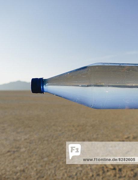 Die Landschaft der Schwarzen Felsenwüste in Nevada. Eine Flasche Wasser. Gefiltertes Mineralwasser. Seitlich. Der Wasserspiegel passend zum Horizont.