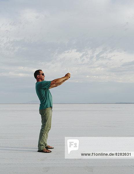 Ein Mann  der in der Abenddämmerung auf den Bonneville-Salinen steht und mit einem Tablettengerät fotografiert.