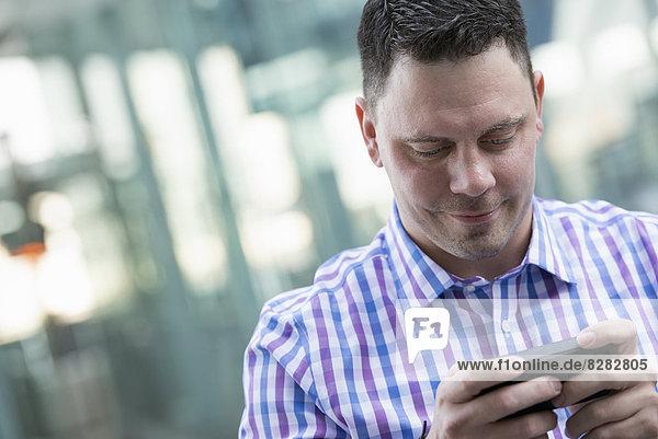 Sommer in der Stadt. Geschäftsleute in Freizeitkleidung. Ein Mann  der sein Telefon überprüft.