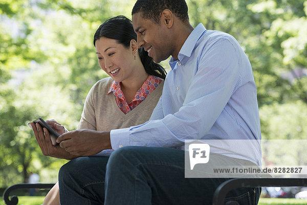 Sommer. Geschäftsleute. Ein Mann und eine Frau sitzen auf einer Bank und benutzen ein Smartphone.