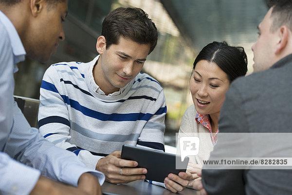 Geschäftsleute in Bewegung. Vier Personen haben sich zu einer Diskussion um ein digitales Tablet versammelt.