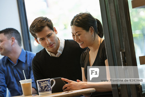 A Group Of People Sitting Around A Table In A Coffee Shop. Looking At The Screen Of A Digital Tablet. Two Men And A Woman.